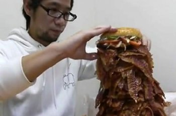 Man eating sandwich with 1000+ slices of bacon. He likes his menus stuffed that tight, too.